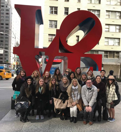 AMDT students outside in front a sculpture of the word love