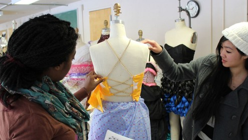 Two students look at the back on a mannequin displayed with yellow fabric and gold chains