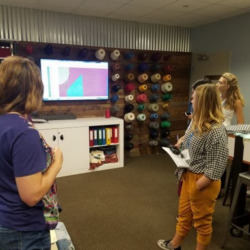 Presenter at Cotton Incorporated showing students the various yarn colors.